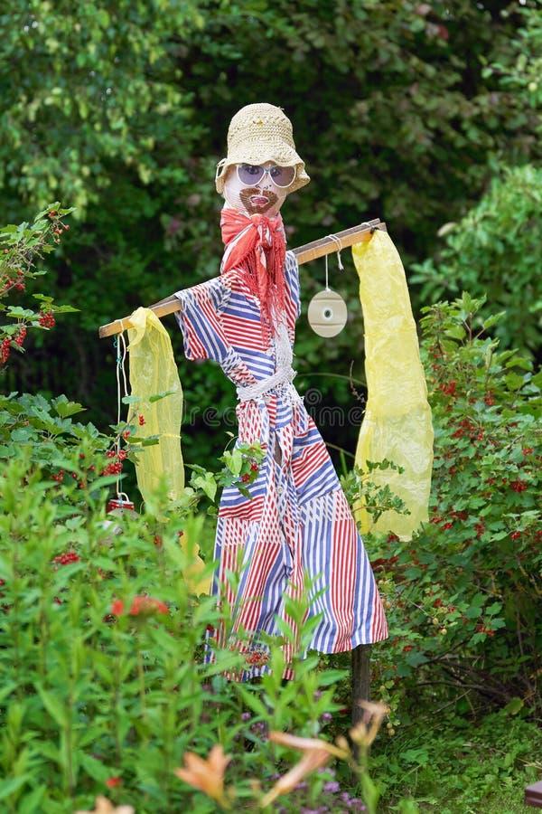 L'épouvantail fabriqué à la main des enfants pour protéger des buissons de groseille rouge contre les oiseaux sur l'attribution photo stock