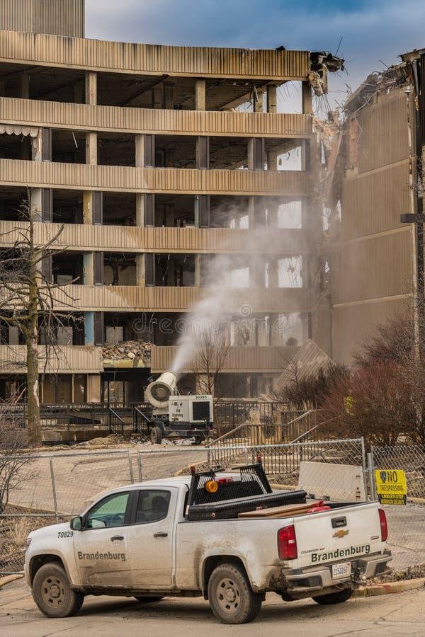 L'équipage de démo pulvérise l'eau pour éliminer la poussière dans la démolition du vieil hôpital croisé argenté photo stock