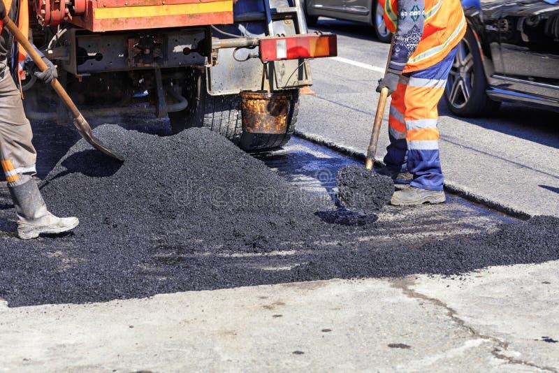 L'équipage travaillant distribue également l'asphalte chaud avec des pelles manuellement sur le site réparé de la route photos libres de droits