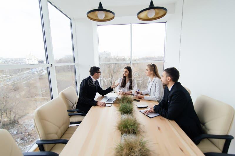 L'équipe écoutent au chef de réunion du projet à la table de conférence image libre de droits