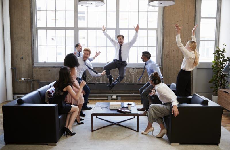 L'équipe d'affaires sautent pour la joie à frapper la cible lors de la réunion image libre de droits