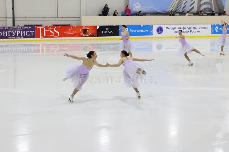 L'équipe dans des robes exécutent au patinage synchronisé par tasse Open images libres de droits
