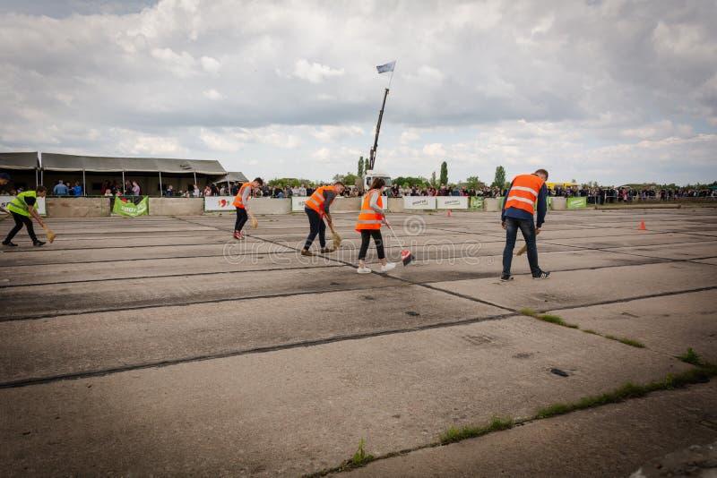L'équipe de décapants dans des vestes oranges nettoie le champ de courses sur des voitures de course d'entrave dans le Transnistr images libres de droits