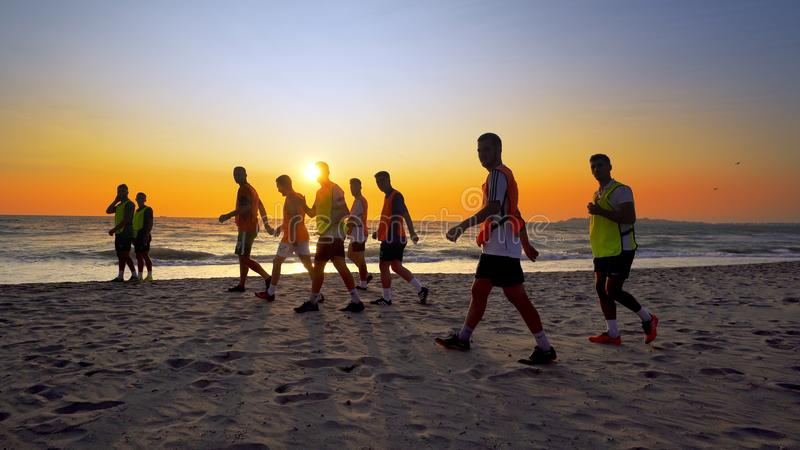 L'équipe de football, donnant des leçons particulières au fonctionnement de formation extérieur sous le coucher du soleil de plag photos stock