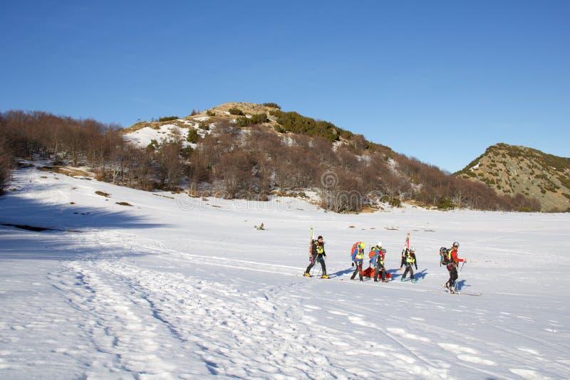 L'équipe de secours de ski amène la personne blessée sur le toboggan et descend à la vallée image libre de droits