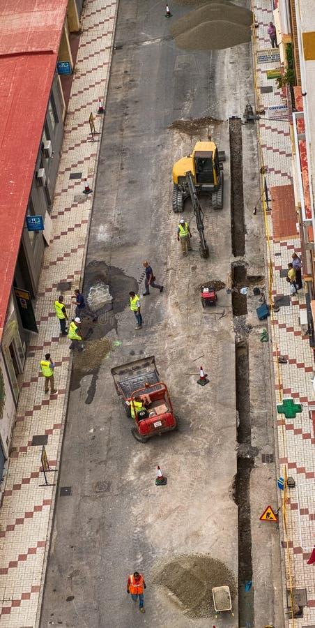 L'équipe de travailleurs travaille pour réparer une conduite d'eau cassée dans la route photos stock