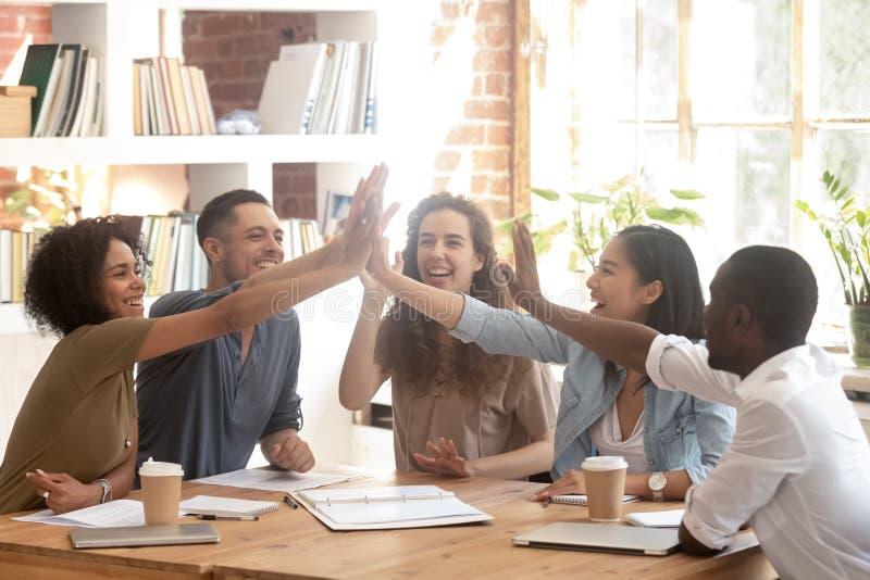 L'équipe ethnique multi heureuse d'affaires joignent des mains donnant haut cinq photos stock