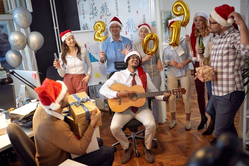L'équipe heureuse d'affaires ont l'amusement et la danse dans le chapeau de Santa à la partie de Noël images libres de droits