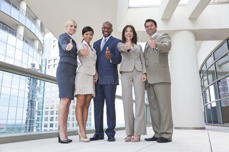 L'équipe interraciale d'affaires d'hommes et de femmes manie maladroitement vers le haut photo libre de droits