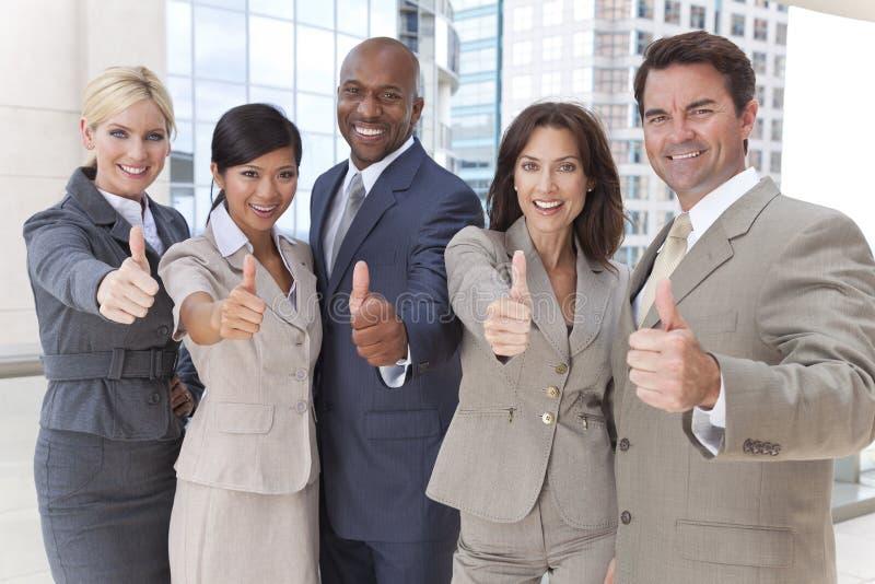 L'équipe interraciale d'affaires d'hommes et de femmes manie maladroitement vers le haut photos libres de droits