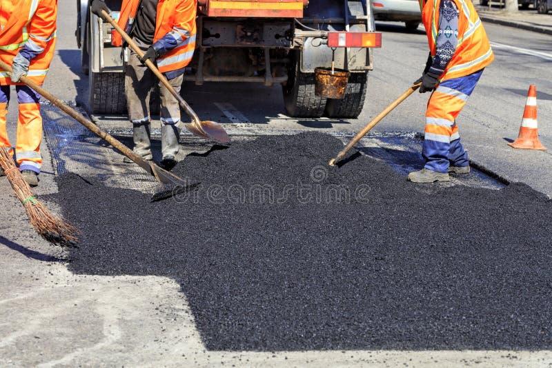 L'équipe travaillante lisse l'asphalte chaud avec des pelles à la main en réparant la route images libres de droits