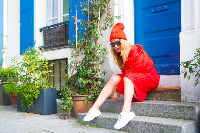 L'équipement élégant de femme se reposent sur des escaliers près de la rue pittoresque de maison d'entrée à Paris Paris connu sou images stock