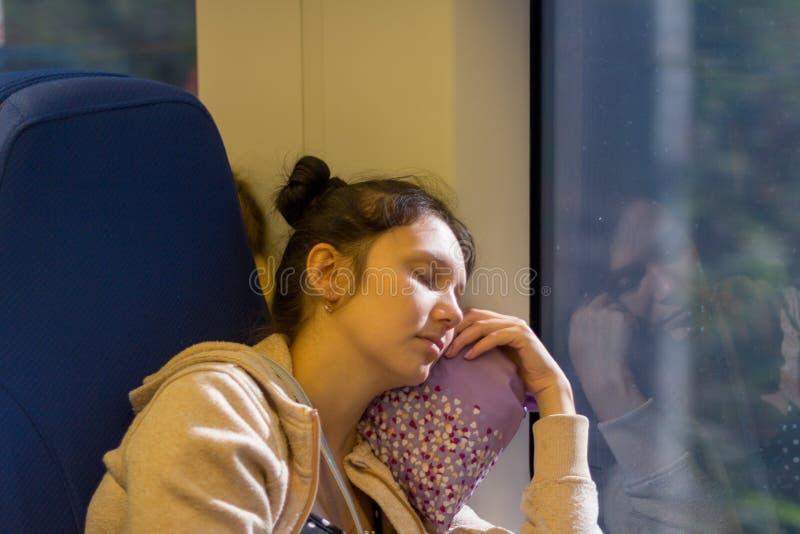 L'équitation de jeune femme de sommeil dans le train électrique ultra-rapide Lastochka pendant l'été image libre de droits
