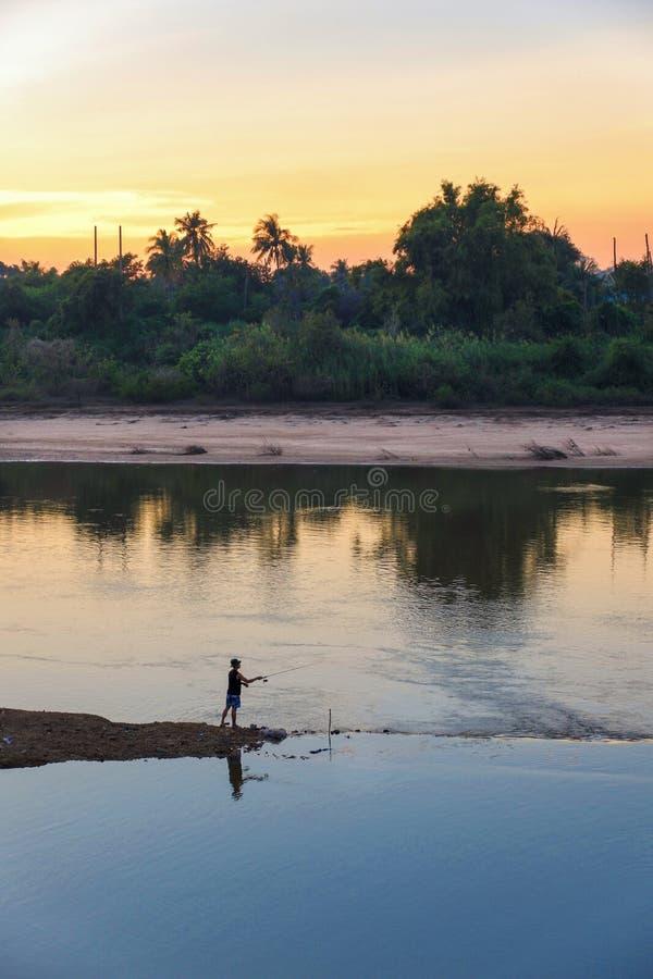 L'été de sport d'hommes de pêcheur de lac de canne à pêche leurrent l'OU de l'eau de coucher du soleil image stock