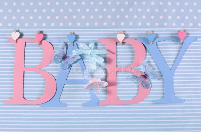 L'étamine rose et bleue de bébé de thème marque avec des lettres pendre des chevilles sur une ligne photo libre de droits