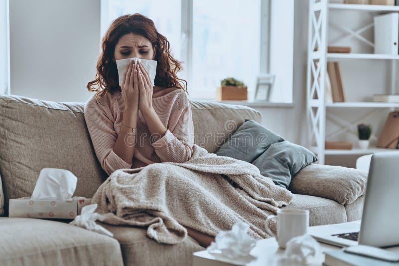 L'éternuement juste continuent à venir Jeunes femmes malades soufflant son nez utilisant les tissus faciaux tout en se reposant s photos stock
