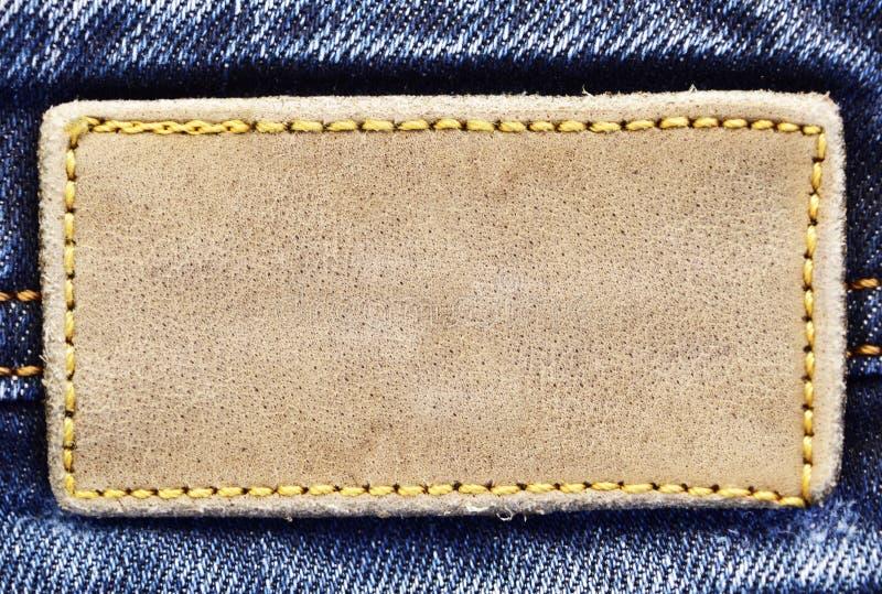 L'étiquette en cuir blanc de jeans a cousu sur les jeans photographie stock libre de droits