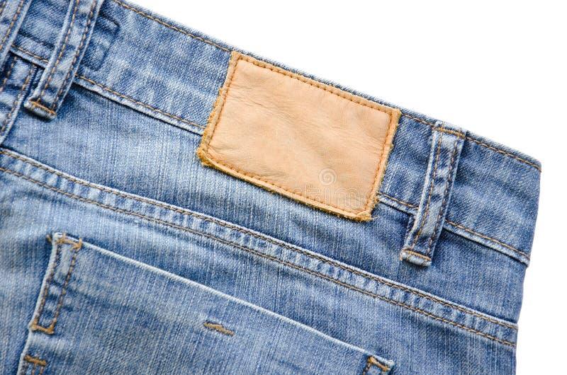 L'étiquette en cuir blanc de jeans a cousu sur les jeans image libre de droits