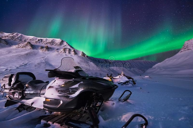 L'étoile arctique polaire de ciel d'aurora borealis de lumières du nord en montagnes de snowscooter de ville de la Norvège le Sva photo stock