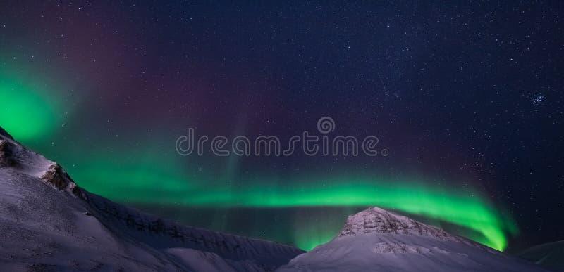 L'étoile arctique polaire de ciel d'aurora borealis de lumières du nord en montagnes de snowscooter de ville de la Norvège le Sva image libre de droits