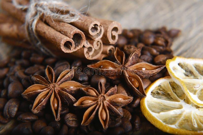 L'étoile en gros plan d'anis, grains de café dispersés, bâtons de cannelle a attaché et a séché des tranches de citron sur le fon image stock