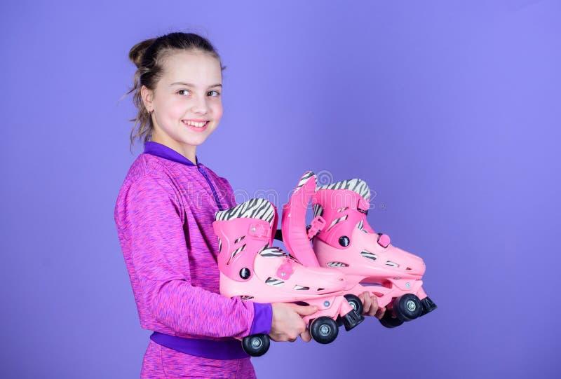 L'étude pour patiner est amusement Petit patineur mignon Petite fille tenant les patins de rouleau roses Peu enfant avec les pati images libres de droits