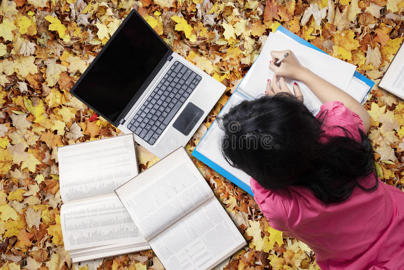 L'étudiant apprend avec l'ordinateur portable sur des feuilles d'automne photographie stock