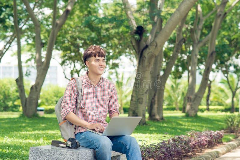 L'étudiant asiatique masculin attirant utilise l'ordinateur dans le ` s d'université photographie stock libre de droits
