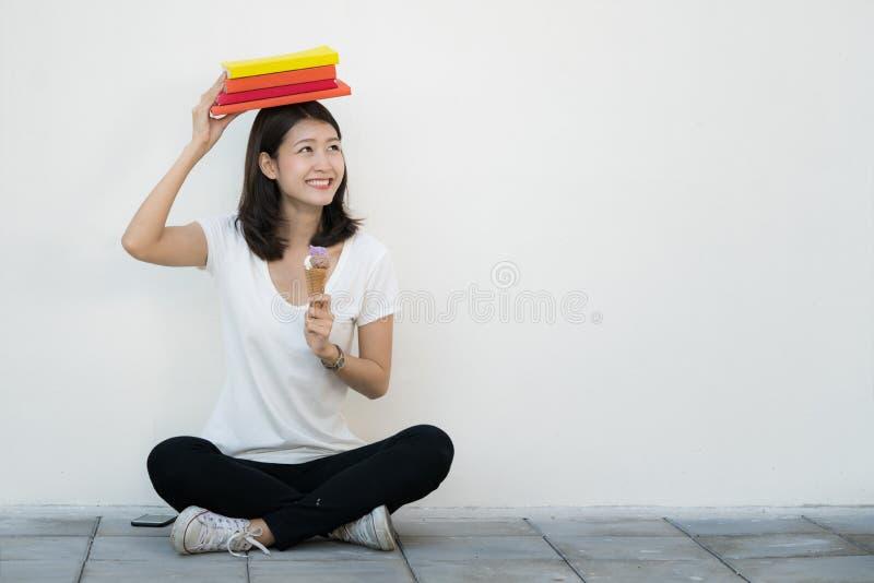 L'étudiant asiatique s'asseyent et détendent avec la crème glacée  photo libre de droits