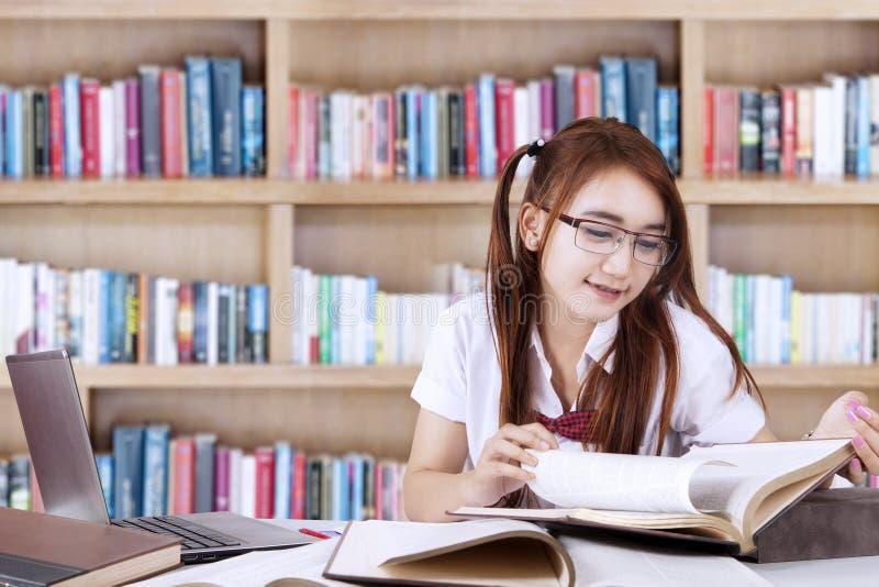 L'étudiant assez adolescent apprend dans la bibliothèque images stock
