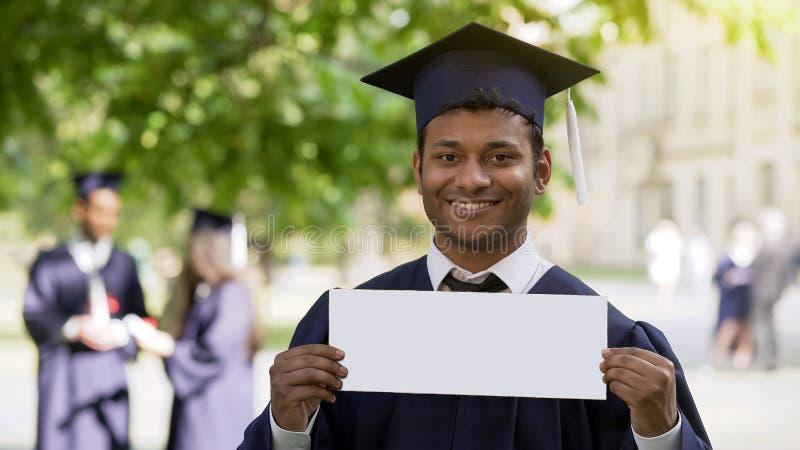 L'étudiant dans des vêtements d'obtention du diplôme mettant vers le haut de la table m'engagent offre d'emploi pour la jeunesse photographie stock