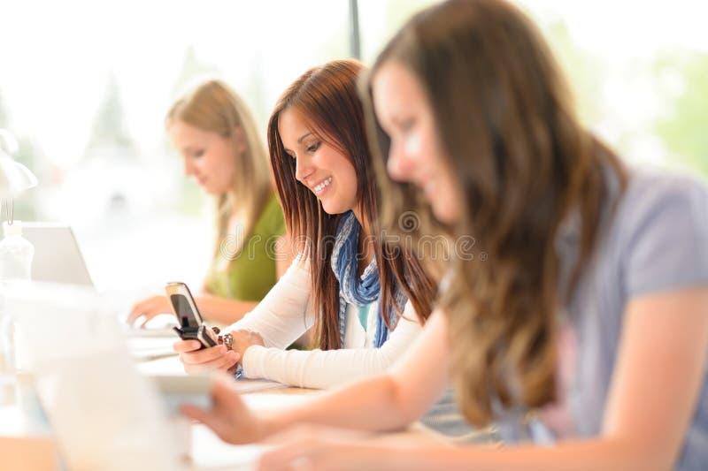 L'étudiant dans la salle de classe utilisant le téléphone écrivent le message image stock