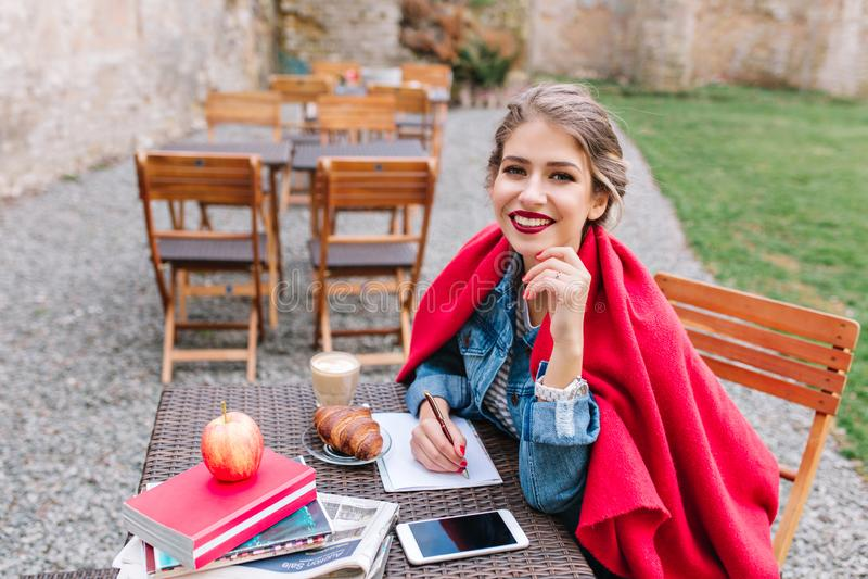 L'étudiant de sourire heureux fait un plan d'étude se reposant dans un café extérieur au temps de petit déjeuner Jeune fille atte image libre de droits