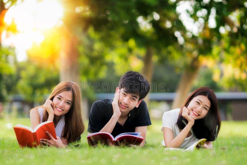 L'étudiant et l'ami asiatiques détendent et lisent un livre à l'université photos libres de droits