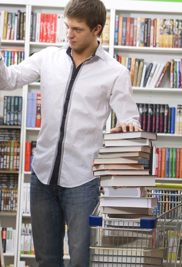 L'étudiant fait des emplettes dans une librairie image stock