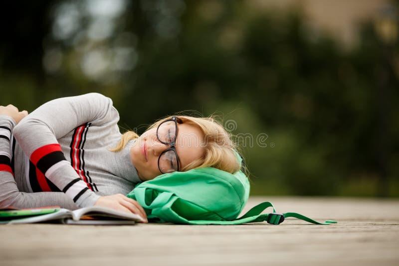 L'étudiant fatigué est tombé endormi pour des manuels dans la cour image stock
