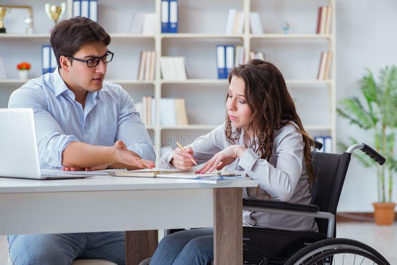 L'étudiant handicapé étudiant et se préparant aux examens d'université photographie stock