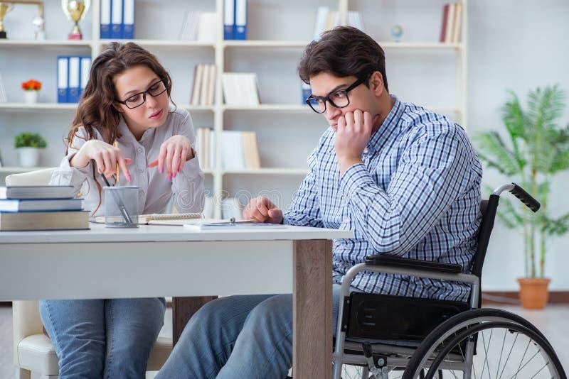 L'étudiant handicapé étudiant et se préparant aux examens d'université image stock