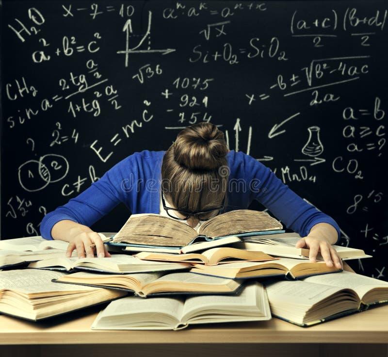 L'étudiant Hard Study, femme ennuyée fatiguée a lu des livres au-dessus de tableau noir photographie stock