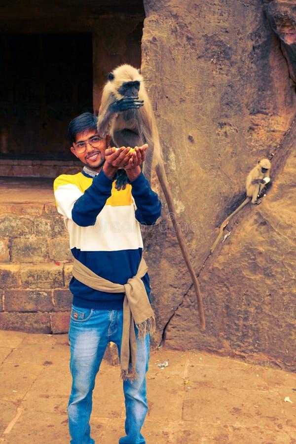 L'étudiant indien alimente le singe à l'entrée d'une de cavernes de Khandagiri à Bhubaneswar photographie stock