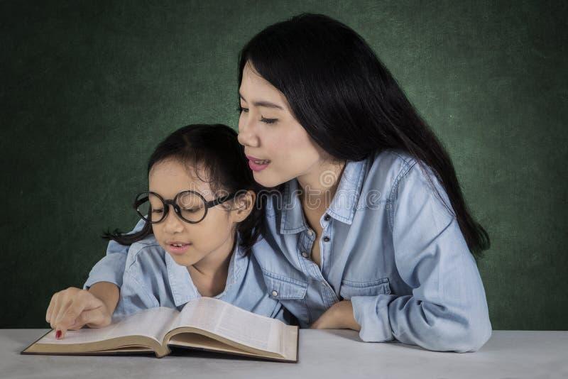 L'étudiant mignon a lu un livre avec le professeur image libre de droits