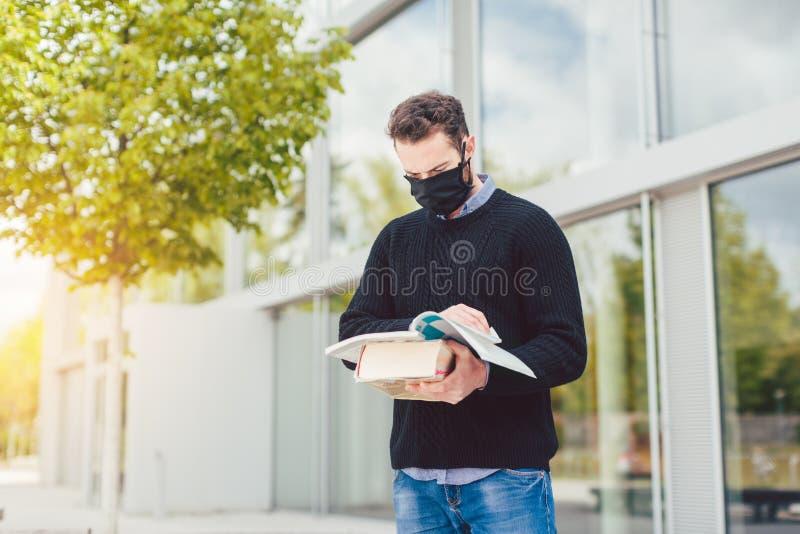 L'étudiant pendant la période 19-19 ne peut pas entrer dans un bâtiment universitaire fermé image stock