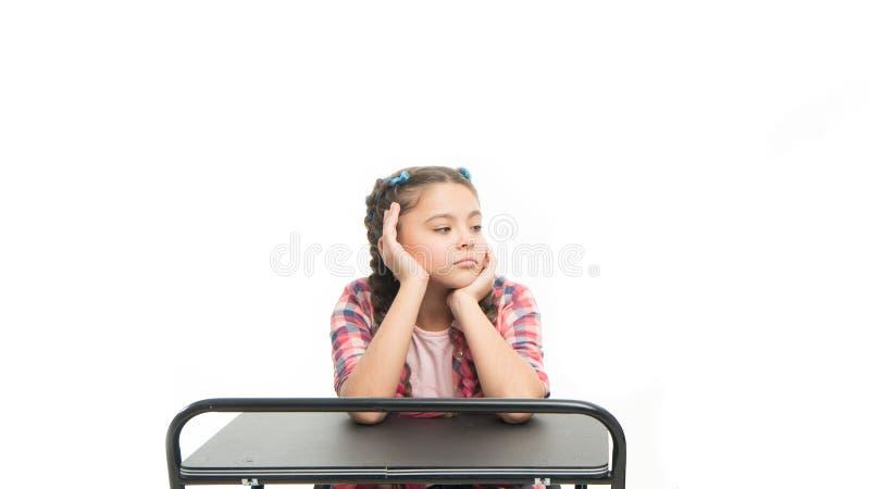 L'étudiant semble ennuyeux Étudiant indifférent d'isolement sur le blanc Petite étudiante s'asseyant au bureau Peu d'étudiant aya images libres de droits