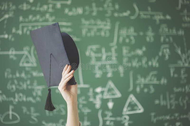 L'étudiant a soulevé le chapeau d'obtention du diplôme de participation de bras devant le panneau de craie vert images libres de droits