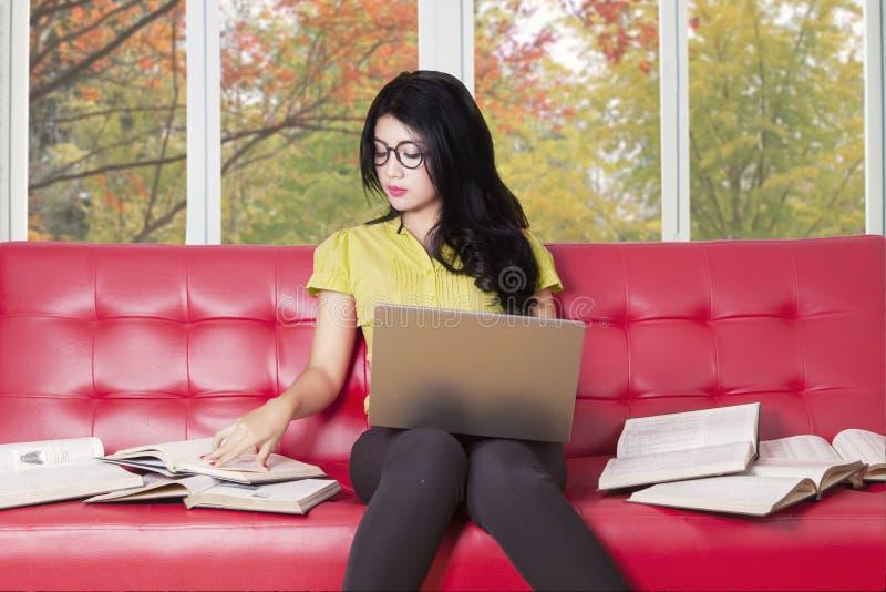 L'étudiant universitaire avec l'ordinateur portable lit des livres sur le sofa images stock