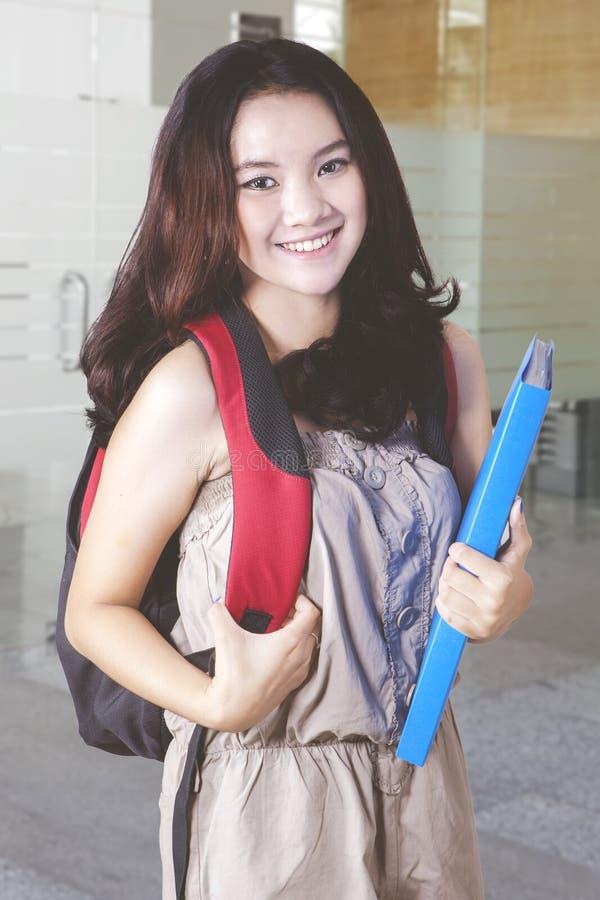 L'étudiant universitaire féminin se tient dans l'école photo libre de droits