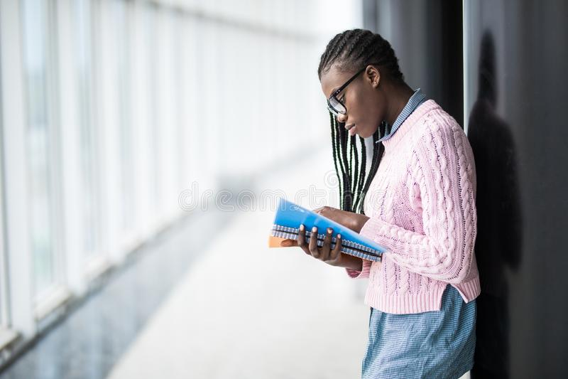 L'étudiante afro-américaine de jeune beauté en verres tenant des carnets et étudiant se préparent à l'examen dans le hall moderne images stock