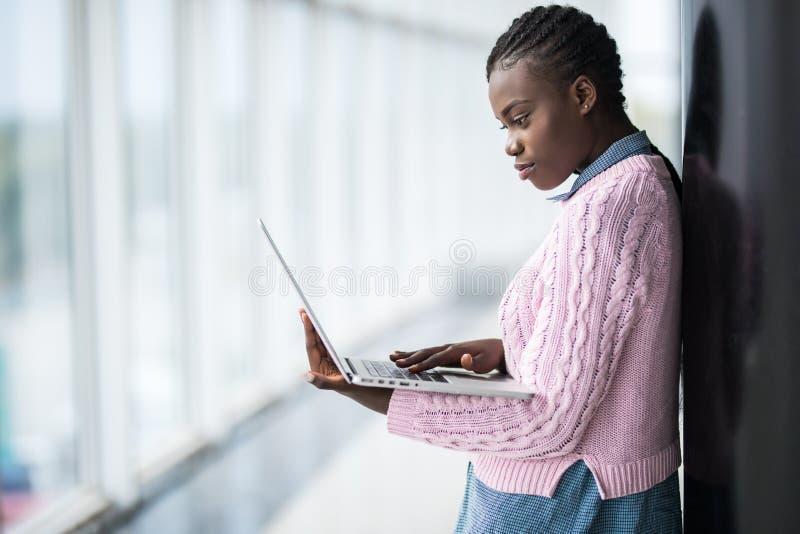 L'étudiante afro-américaine de jeune beauté en verres tenant l'ordinateur portable et étudiant se préparent à l'examen dans le ha image libre de droits