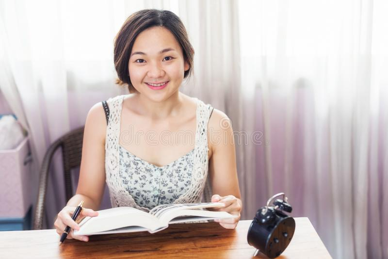 L'étudiante asiatique a lu le livre pour l'examen final photos libres de droits