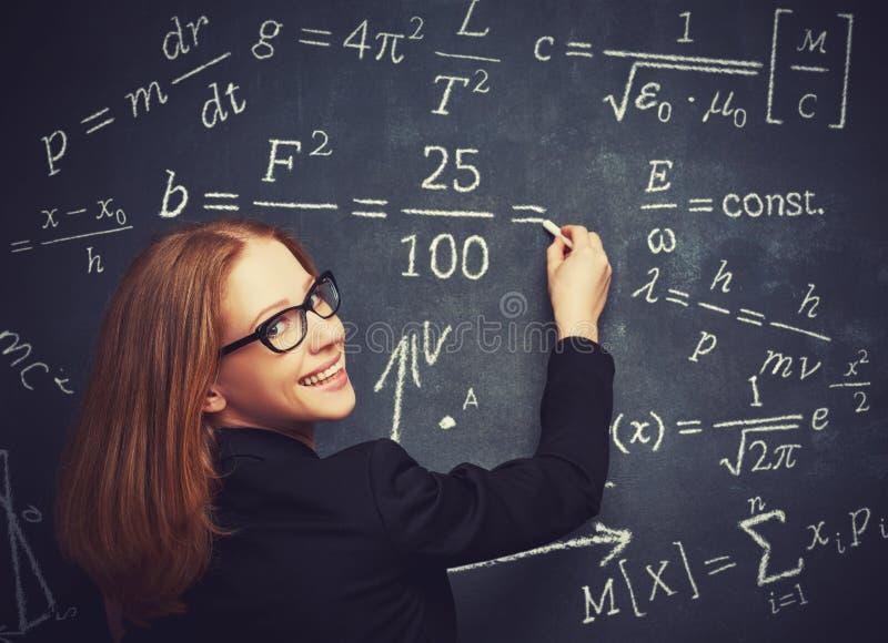 L'étudiante heureuse, le professeur écrit sur la forme de craie de tableau noir images stock
